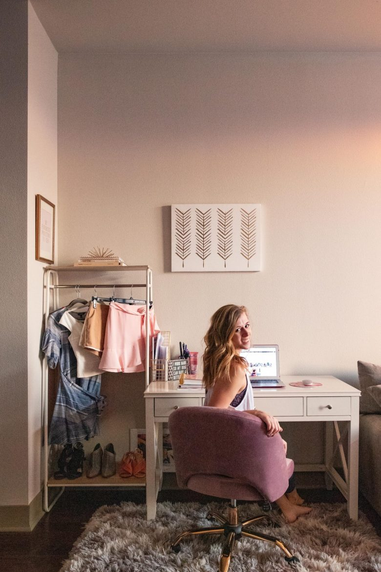 7 Ways to Make the Most of Your Small Home Office Space | Running in Heels | I didn't have much of a choice on size of my home office, but I made the most of my small space with a white desk wiht 3 drawers, a clothing rack, of course a pink chari, and a cozy flokati gray rug for comfort, and lots of natural light! Click to read my other tips for making the most of your small space!