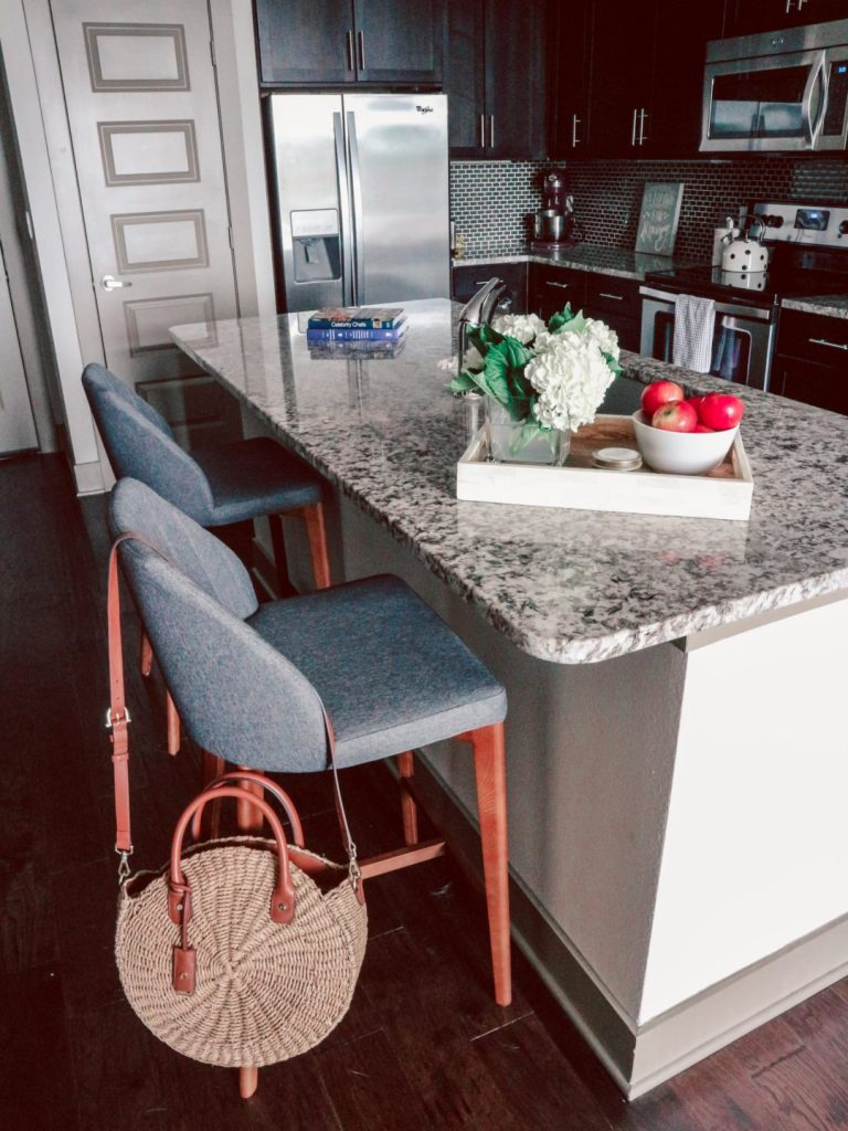 How to Choose the Right Barstools- Because You Don't Need a Kitchen Table | Styled Kitchen Counter with granite kitchen Island with white try filled with hydrangas, bowl of apples, and Craft + Foster candle. Showing grey APT2B barstools in front of wine rack.