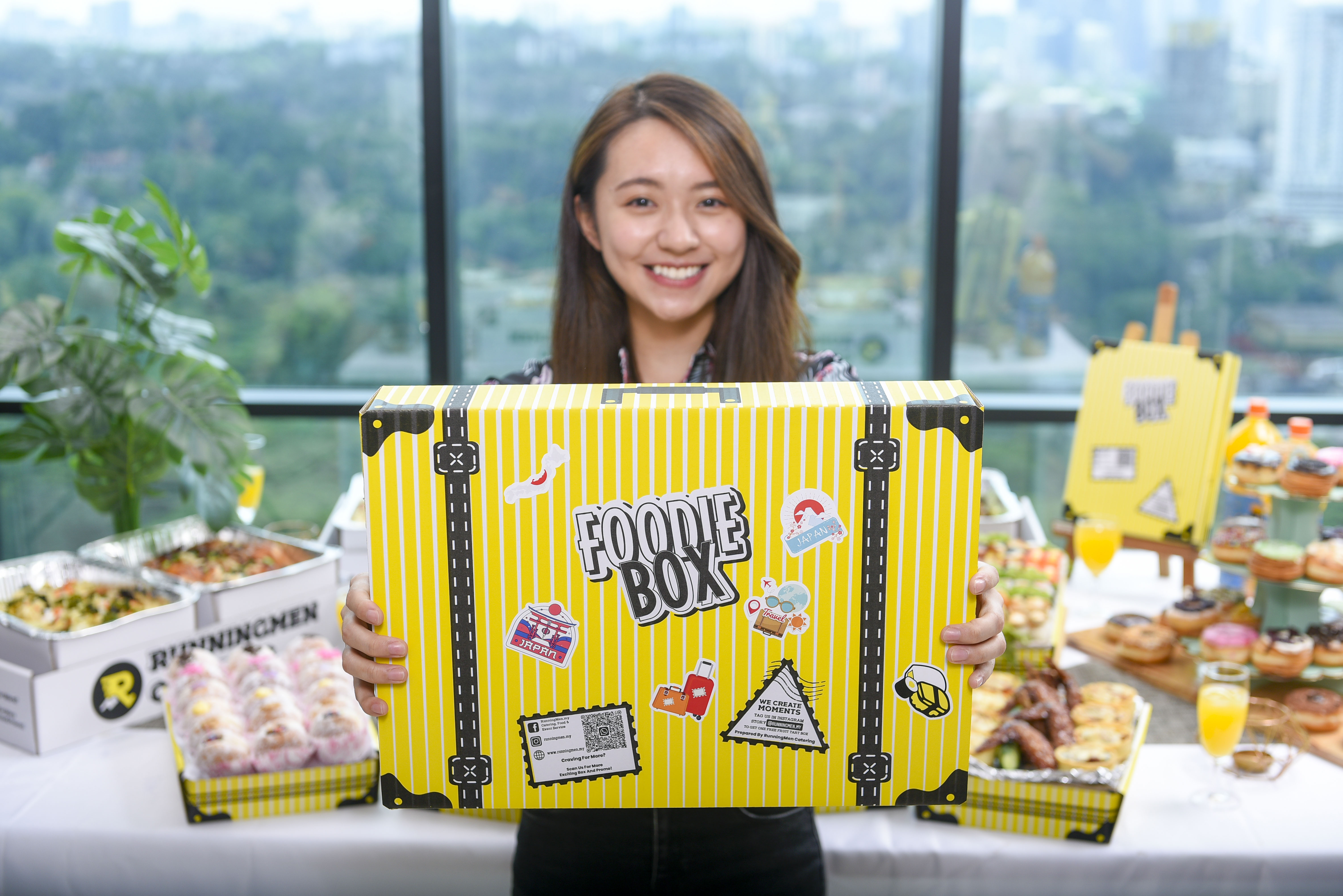 a chinese girl holding runningmen catering's foodie box travel theme luggage box