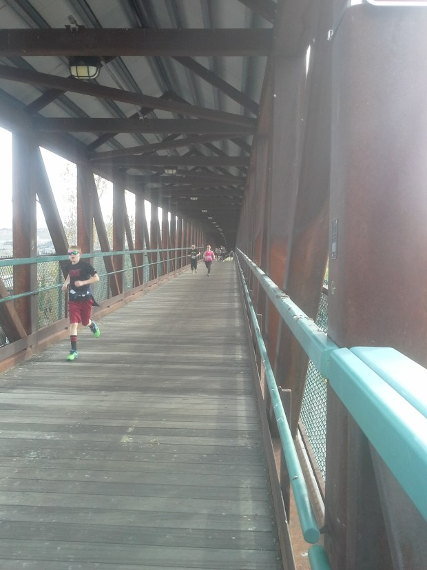 Runners making their way down the pedestrian bridge to the finish line.