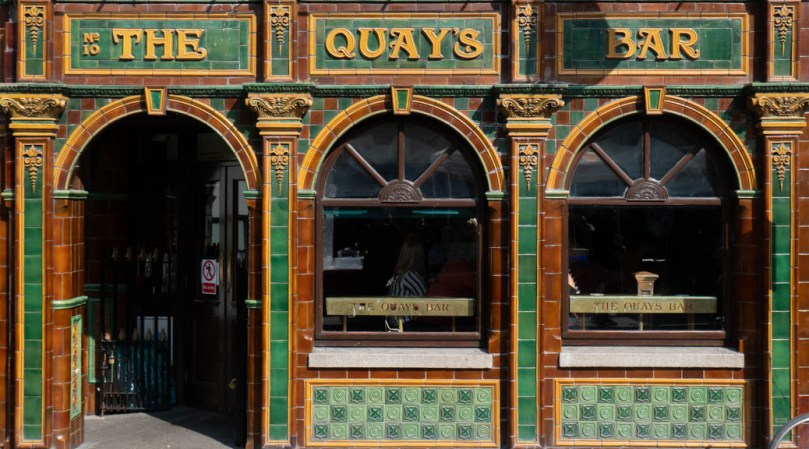 The ground-floor Temple Bar façade of The Quay's Bar, Dublin: a pub facade, tiled in green, brown, and yellow, with an arched doorwy and two arched windows