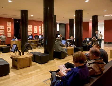 The National Gallery's Espresso Bar, showing a series of ArtStart collection information touch-screen kiosks with audio wands, placed on low tables with stools and a bench with swivel chairs.