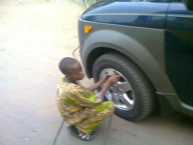Child labour? A boy working as a vulcanizer (apprentice) at college road, ogba, Nigeria.