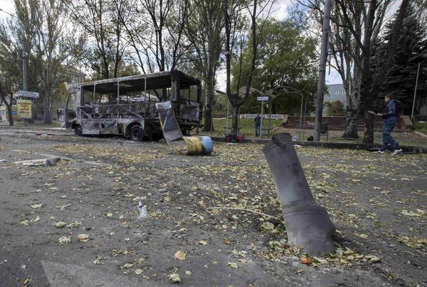 The remains of a rocket shell is seen in front of a burnt-out bus on a street in Donetsk, eastern Ukraine