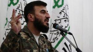 Захран Алюш на фона на знамето на Джейш ал Ислям.