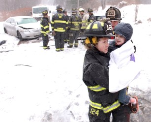 Auburn Firefighter Sita West carries a young boy to a waiting rescue vehicle after he and his father were involved in a head-on collision at 1958 Riverside Drive Monday afternoon shortly after it began snowing.