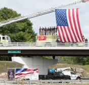 Lewiston firefighters and police officers pay tribute on the overpass on Old Lisbon Road in Lewiston early Wednesday afternoon. They were showing their support for a convoy of vehicles and motorcycles escorting a piece of metal from the World Trade Center in New York City that was being transported to Newfoundland. It will be included in a display at the Gander airport, where 38 planes were diverted and grounded during the 2001 terrorist attacks. The small town rallied together to care for the 6,000 people stranded there as airports in the US were closed.