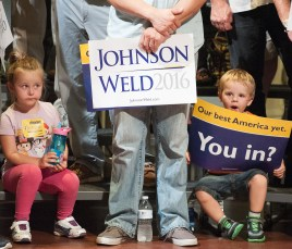 Natalie Staples, left and her brother David, of Brunswick, patiently wait with their father, Dean, center, for Gray Johnson and Bill Weld to arrive at Lewiston's Franco Center Friday night.