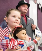 "Lillian Mercier,8 of Minot and her grandfather, Matthew Foster, both from Minot, patiently wait for Donald Trump to arrive at the Open Door Bible School in Lisbon Friday during a campaign rally. Mercier is a student at the school who likes Trump because her father does, while her grandfather said ""He's just what we need, kinda like another Ronald Reagan."""
