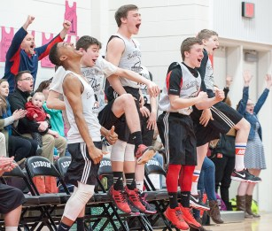 The bench and fans react as a Lisbon Unified Basketball team player scores a basket during Tuesday night's Regional Championship game against Deering/Portland in Lisbon.