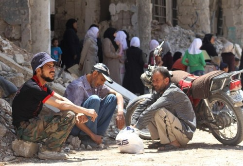 Syrian men sit next to a damaged building in the town of Daraya, southwest of central Damascus, on May 23, 2016.