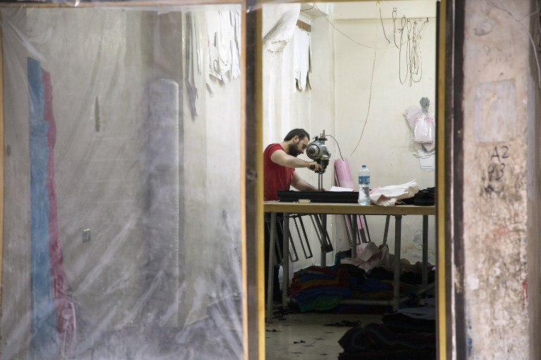 A Syrian man works at his shop behind a front window sealed with plastic tarp in the rebel-held Kallaseh district in the northern city of Aleppo on May 24, 2016.