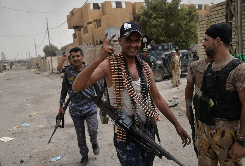 A member of the Iraqi government forces flashes the sign for victory in the besieged city of Fallujah as they hunt down jihadists