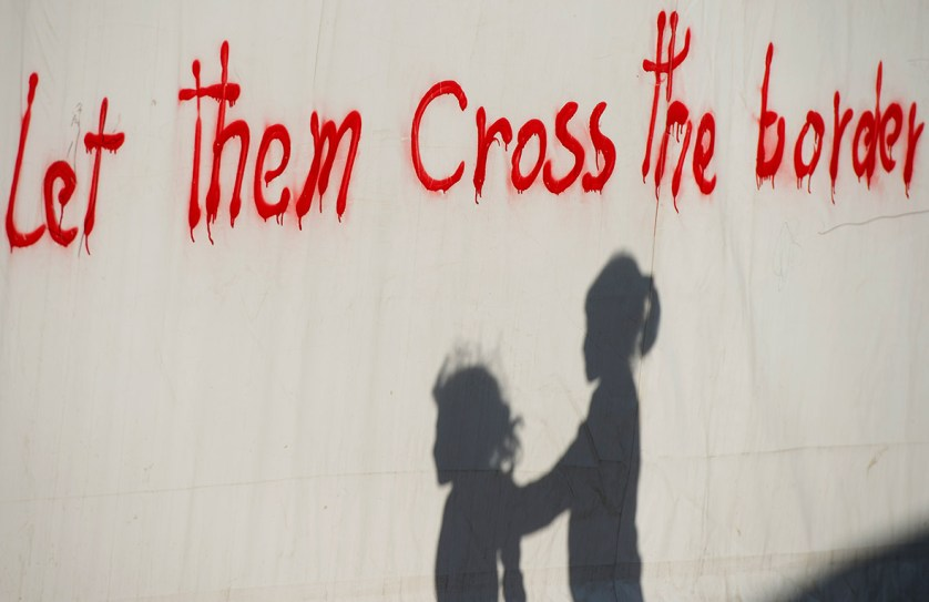 4 May 2016: Children's shadows are seen near graffiti in a makeshift camp for migrants and refugees on the Greek-Macedonian border
