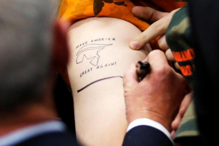 Donald Trump signs a supporter's tattooed arm after a rally in San Diego, California, May 27, 2016. REUTERS/Jonathan Ernst
