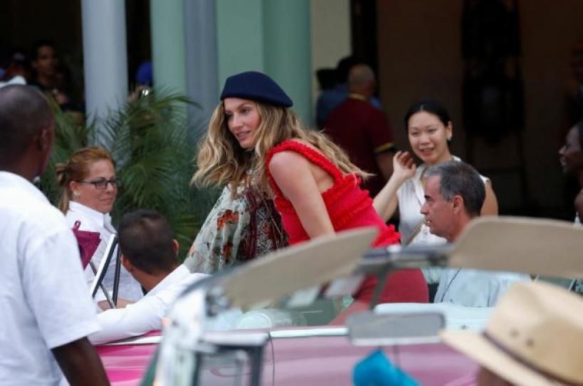 Brazilian supermodel Gisele Bundchen (C) climbs into a vintage car to attend a fashion show by Chanel, the first major fashion house to send models down the catwalk in Cuba, in Havana, May 3, 2016. REUTERS/Stringer