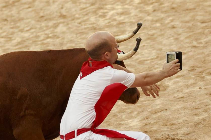 A reveler is tossed as he tries to get a photo next to a bull in the bullring after the running of the bulls in the 2016 San Fermin fiestas in Pamplona, Spain on July 7. Revelers from around the world kicked off the festival in the Pamplona town square, one day before the first of eight days of the running of the bulls.