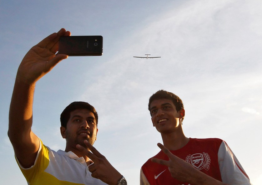 18 March 2015: Two youths take a picture of themselves with Solar Impulse 2 as it takes off from Ahmedabad en route to the northern Indian city of Varanasi for a stop, before heading to Myanmar