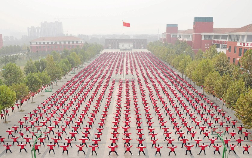 Students practice tai chi on a playground at a high school in Jiaozuo, Henan province, China, during a Guinness World Record attempt for the largest martial arts display, on 18 October 2015