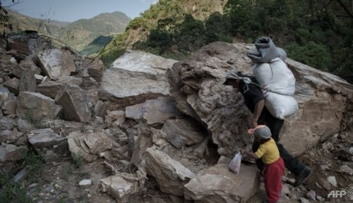 A file photo shows a Barpak villager with his son passing through a landslide as they trek up the mountain carrying a foam mattress, food and other goods to his village, between Baluwa and Mandre village in north central Nepal.