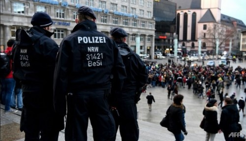 Police look on as refugees demonstrate against violence near the main Cologne train station, where hundreds of women were groped and robbed by mostly Arab and North African men during New Year festivities
