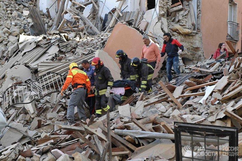 Сотрудники спасательных служб извлекают из-под завалов людей, пострадавших в результате землетрясения.