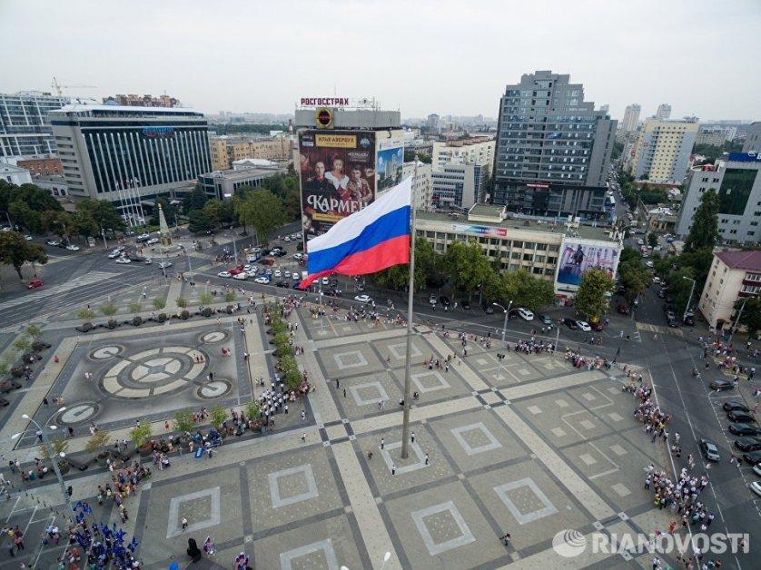 На Театральной площади Краснодара в честь праздника в торжественной обстановке подняли гигантский триколор.