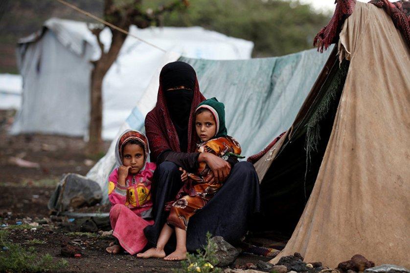 Женщина с детьми у палатки в лагере для беженцев неподалеку от Саны, Йемен.