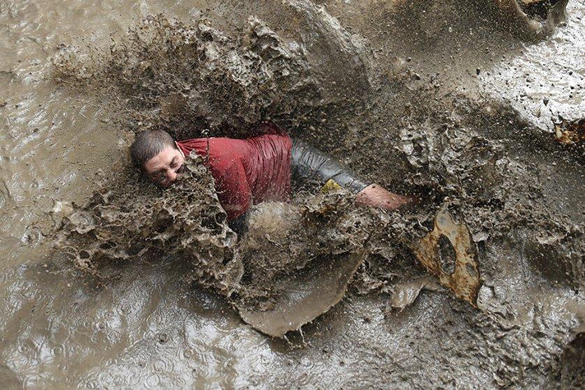 Участник 13-километрового забега по случаю Дня грязи в городе Мериньяк, юго-западе Франции.