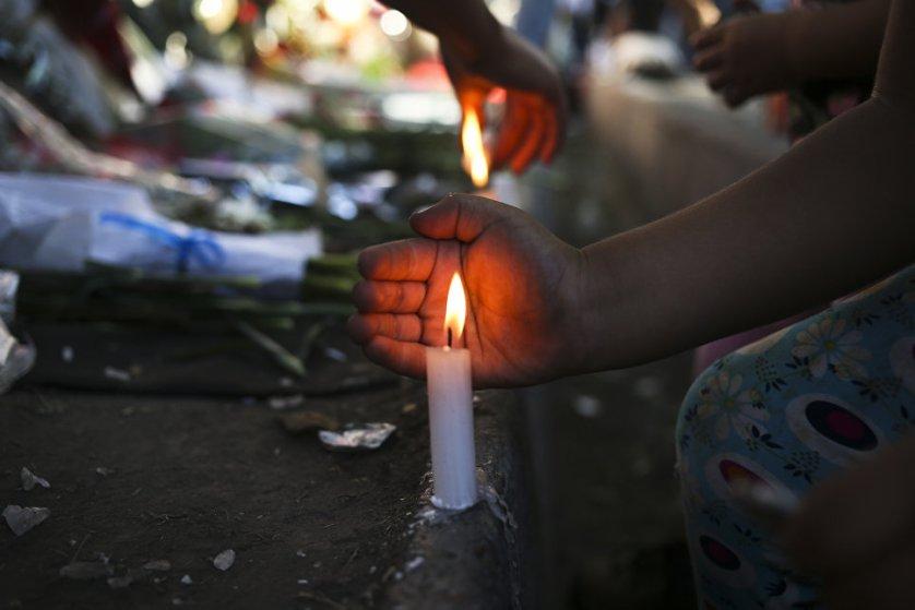 Жители Сантьяго зажигают свечи в память о Фиделе Кастро перед посольством Кубы.