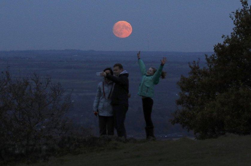 Семья фотографируется на фоне луны, Лафборо, Великобритания.