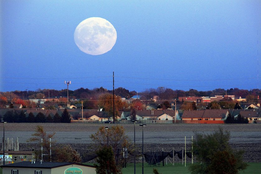 Луна поднимается над Спрингфилдом, штат Иллинойс, США.