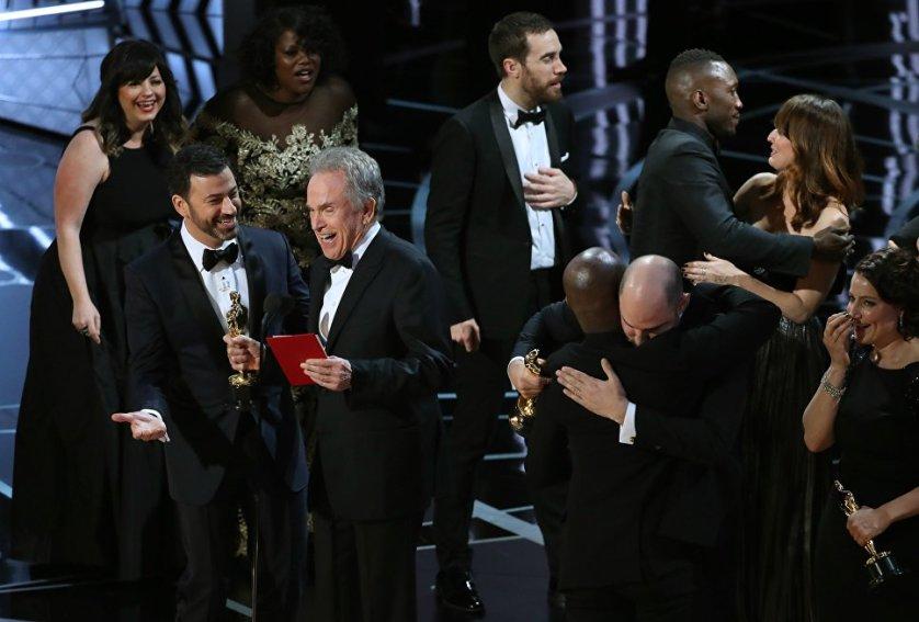 """Ведущий церемонии Джимми Киммел просит прощения у Уоррена Битти за то, что дал ему не тот конверт с названием фильма-победителя. В это время режиссер фильма """"Лунный свет"""" Барри Дженкинс благодарит за внезапно доставшуюся ему статуэтку продюсера ленты """"Ла-Ла Ленд"""" Джоржана Хоровица."""