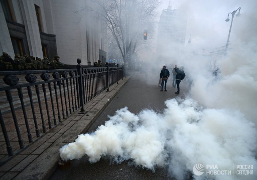 Ранее националисты прошли маршем от майдана Незалежности к зданию парламента, участники шествия жгли дымовые шашки.