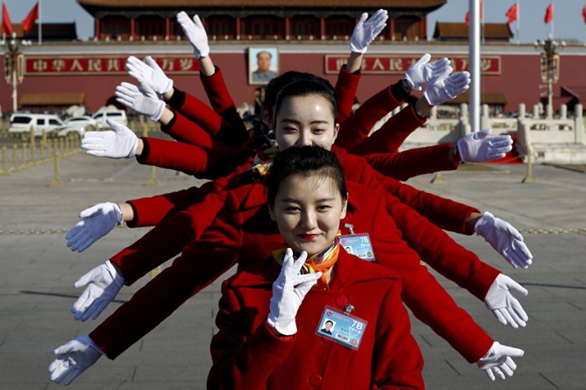 Девушки, работающие с делегатами во время Национального народного Конгресса, позируют фотографам на площади Тяньаньмэнь в Пекине.
