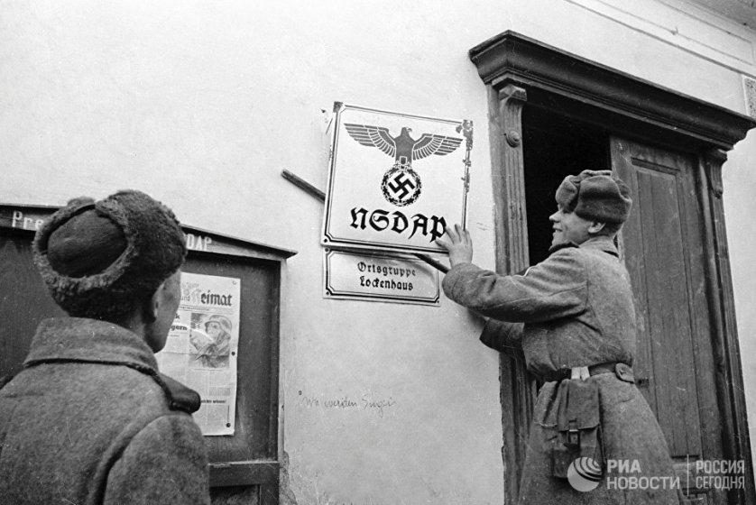 Советские бойцы в австрийском селении Лекенгауз срывают вывески с фашистских учреждений. 26 апреля 1945 года.