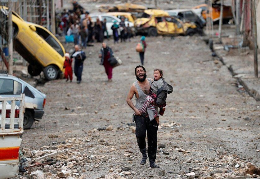 Отец бежит с дочерью на руках с подконтрольных боевикам ИГ (организация запрещена в России) территорий во время битвы за Мосул.