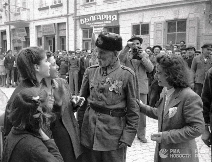 Ветеран турецкой войны беседует с девушками в болгарском городе, освобожденном от фашистов войсками Красной армии. 24 сентября 1944 года.