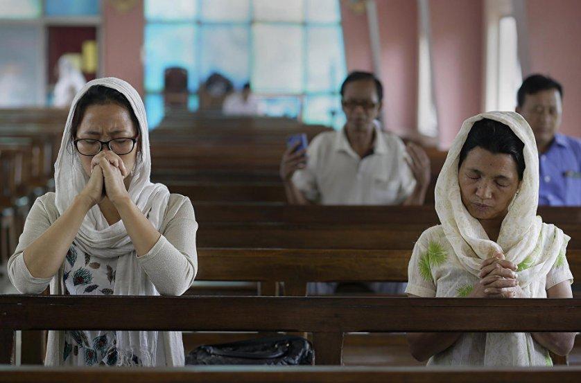 """Начиная с пасхальной ночи и последующие сорок дней принято приветствовать друг друга словами: """"Христос воскресе!"""" — """"Воистину воскресе!"""". На фото: верующие молятся на богослужении в Индии."""