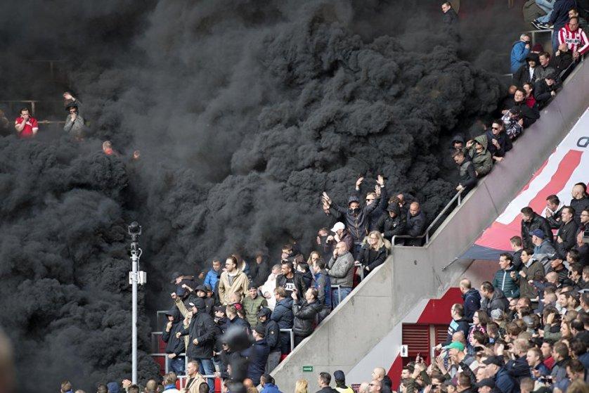 """Футбольный матч ПСВ """"Эйндховен"""" – """"Аякс"""" в Амстердаме. После того, как болельщики нидерландского клуба использовали дымовые шашки трибуны окутал черный дым."""