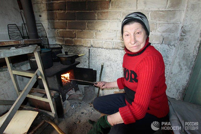 Местной жительнице приходится готовить еду на буржуйке, установленной в подъезде пострадавшего от обстрелов многоквартирного дома.