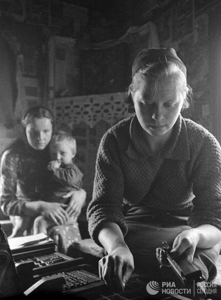 Не отрываясь от хозяйства, некоторые девушки становились наборщицами в партизанских отрядах. На фото: в подпольной типографии набирается текст для печати листовок.