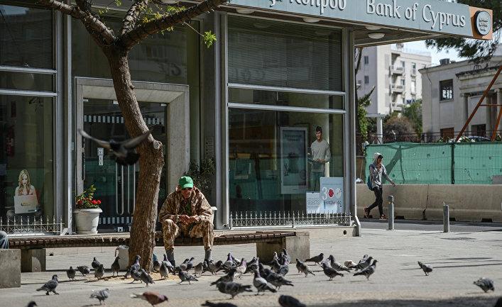 Мужчина кормит голубей у закрытого офиса Bank of Cyprus в Никосии