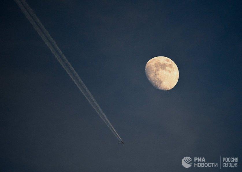Конденсационный след от самолета на фоне луны в небе над Будапештом.