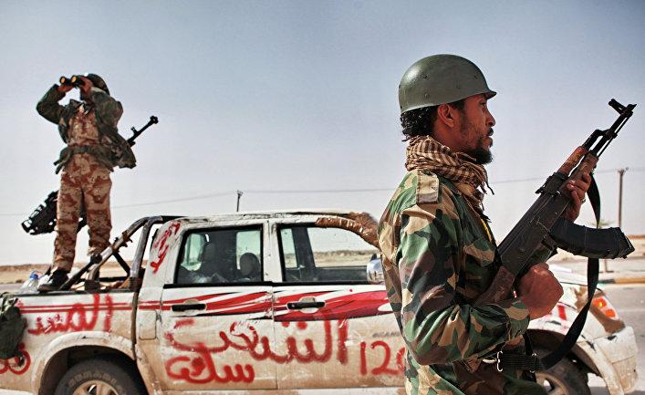 Боец оппозиции и наблюдатель с биноклем в городе Аждабия.