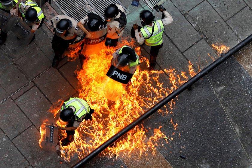 Протестующие подожгли сотрудников полиции во время митинга против президента Венесуэлы Николаса Мадуро в Каракасе.