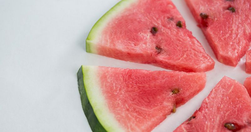 Slices of watermelon arranged on white background