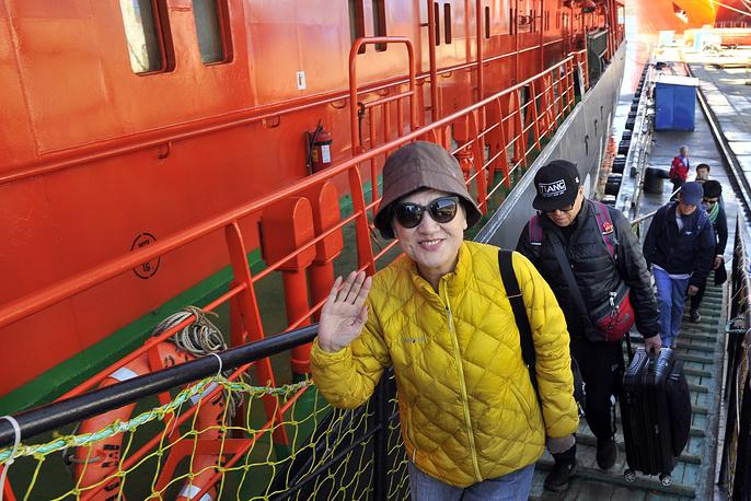 """MURMANSK, RUSSIA - JUNE 15, 2017: Passengers board Atomflot's 50 Let Pobedy [50th Anniversary of Victory] nuclear ice breaker ahead of her first Arctic cruise this year, 125 tourists from Europe and Asia aboard for eleven days. Lev Fedoseyev/TASS Ðîññèÿ. Ìóðìàíñê. 15 èþíÿ 2017. Òóðèñòû ïîäíèìàþòñÿ íà áîðò àòîìîõîäà """"50 ëåò Ïîáåäû"""" ïåðåä îòïðàâëåíèåì â ïåðâûé â ýòîì ãîäó òóðèñòè÷åñêèé êðóèç íà Ñåâåðíûé ïîëþñ. Íà áîðòó àòîìîõîäà íàõîäèòñÿ 125 òóðèñòîâ èç Åâðîïû è Àçèè, ïðîäîëæèòåëüíîñòü êðóèçà ïî ìàðøðóòó Ìóðìàíñê - Ñåâåðíûé ïîëþñ - Ìóðìàíñê ñîñòàâëÿåò 11 ñóòîê. Ëåâ Ôåäîñååâ/ÒÀÑÑ"""