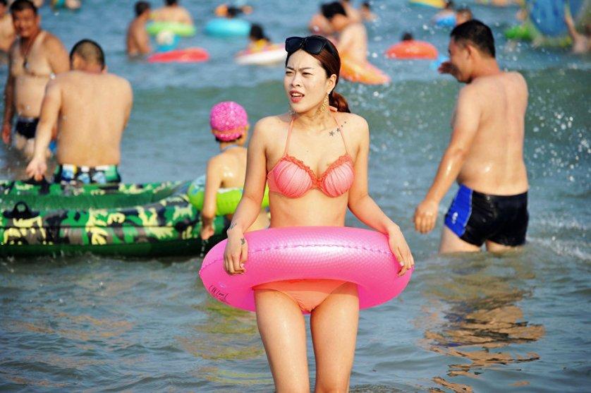 Девушка на пляже в Циндао, Китай.