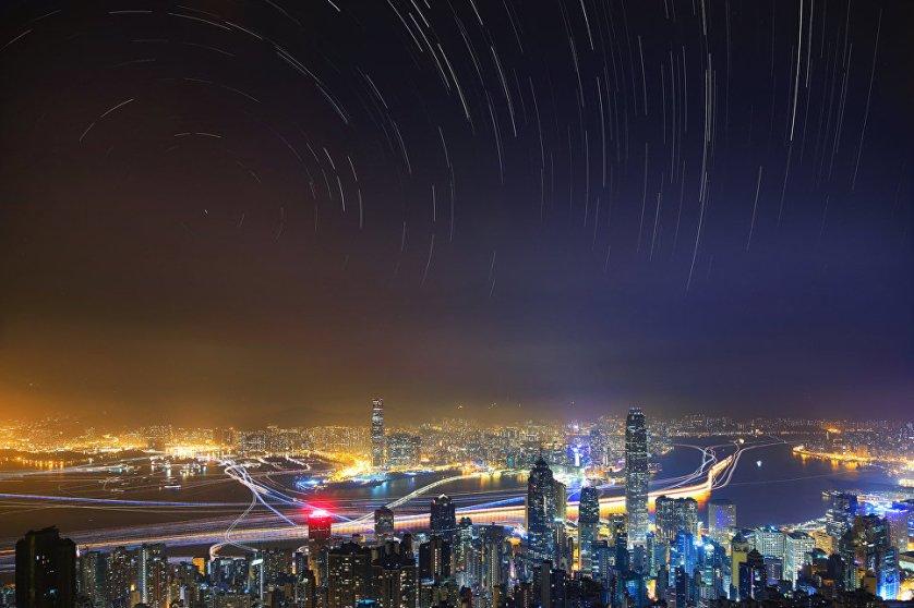 """Работа фотографа Prisca Law """"Суета и спокойсткие"""" (Hustle and Peaceful). Снимок был сделан с самый высокой точки Гонконга. На кадре суета и шум города противопоставлены умиротворению спокойного звездного неба. Фотограф напоминает, что именно смог города мешает в полной мере любоваться потрясающим видом звезд."""